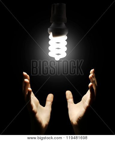 Hands with energy saving light bulb on black background