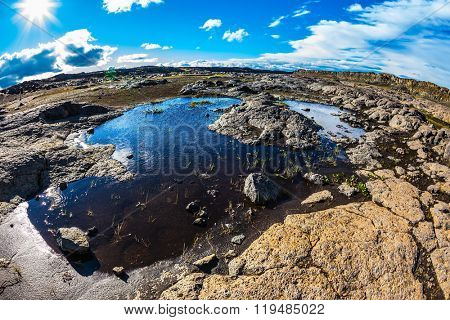 Picturesque small puddle in which is reflected the blue sky. Photo taken fisheye lens. Iceland, Jokulsargljufur National Park