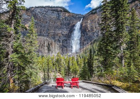 Two wooden red deckchairs for tourists opposite the famous waterfall. Autumn day in Yoho National Park in the Rocky Mountains of Canada