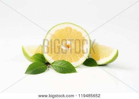 sliced green grapefruit on white background