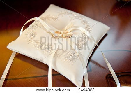 Two amazing golden shiny rings jewel for nuptials ceremony laying on white beautiful pillow with bow
