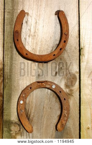 Two Horseshoes On A Wooden Background.