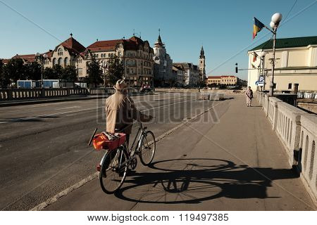 ORADEA, ROMANIA - AUGUST 01, 2015: in the morning an elderly man with boater and bicycle crossing on foot the bridge on the Crisul Repede River that leads to the Union Square of the Oradea town