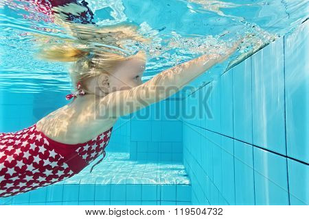 Little Child Diving Underwater In The Pool