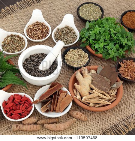 Healing herb and spice selection used in natural alternative herbal medicine for men over hessian background. Selective focus.