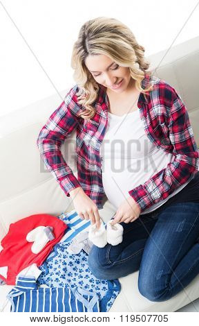 Young attractive pregnant woman playing with babies shoes.