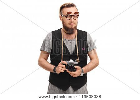 Studio shot of a young male hipster holding a camera and posing isolated on white background