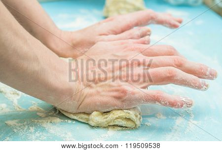 Women's hands knead the dough for pizza