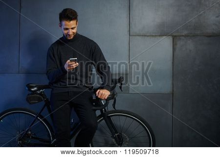 Young man waiting, leaning against bicycle, using mobilephone.