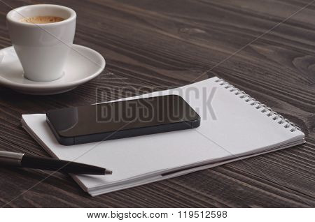 Black Smart Phone On Wooden Dark Background With Notebook