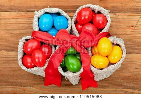 Colorful Easter Eggs In Small Burlap Sacks