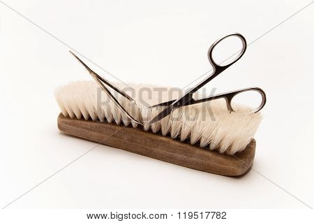 Wooden scrub brush is trimmed by scissors, conceptual