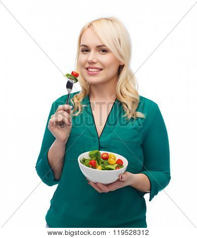 healthy eating, food, diet and people concept - smiling young woman eating vegetable salad with fork