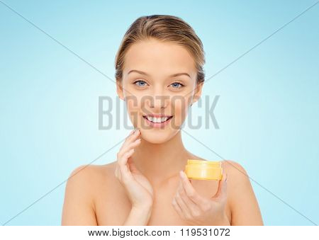 beauty, people, cosmetics, skincare and cosmetics concept - happy young woman applying cream to her face over blue background