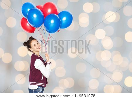 people, teens, holidays and party concept - happy smiling pretty teenage girl with helium balloons over lights background