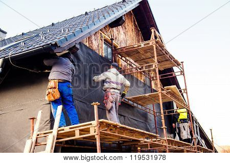 Construction workers thermally insulating house with glass wool