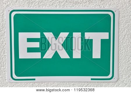 Green Emergency Exit Sign On A Wall. Label That Will Help You Escape