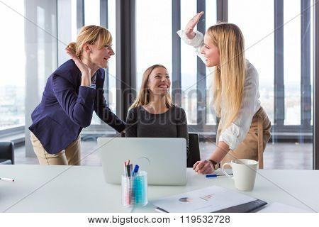 Three business women in modern office celebrating good project results.