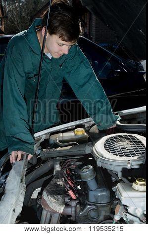 Teenage Boy Looking At A Car Engine