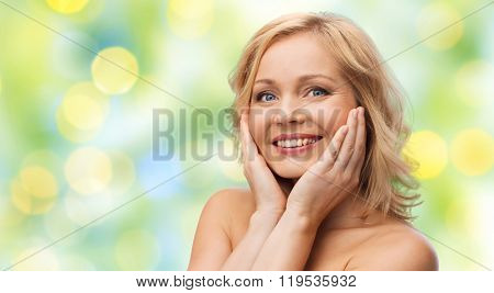 beauty, people and skincare concept - smiling woman with bare shoulders touching face over green summer lights background