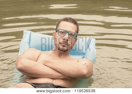 Serious hipster guy in the lake.