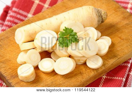 close up of sliced root parsley on wooden cutting board