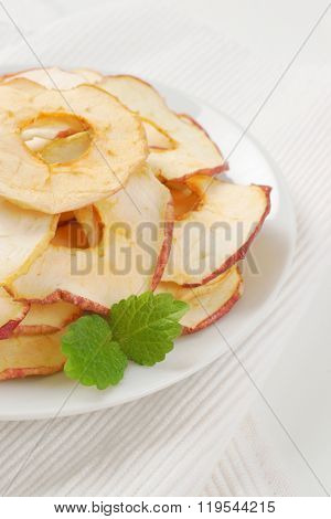 plate of dried apple chips on white place mat - close up