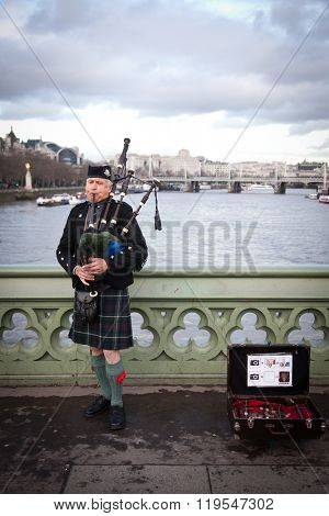 LONDON - January 4, 2016:: Unidentified bagpiper on the Westminster Bridge on Feb 16, 2016 in London.