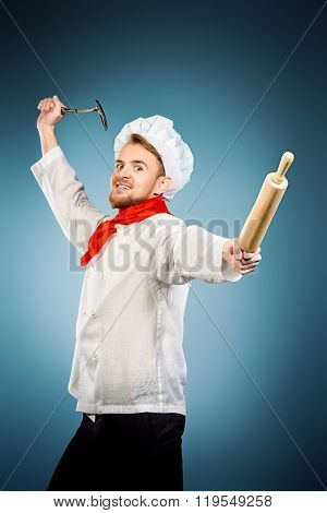 Enraged chef cook brandishing with ladle and a rolling pin. Studio shot.