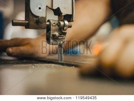 Craftsman Cutting An Iron Rod Using A Hacksaw.