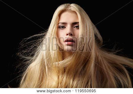 Portrait of blonde girl with flying hair on black background