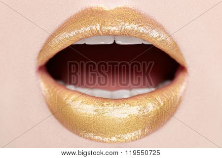 Close-up lips make-up with gold. Open mouth