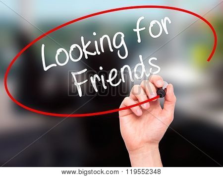 Man Hand Writing Looking For Friends With Black Marker On Visual Screen.