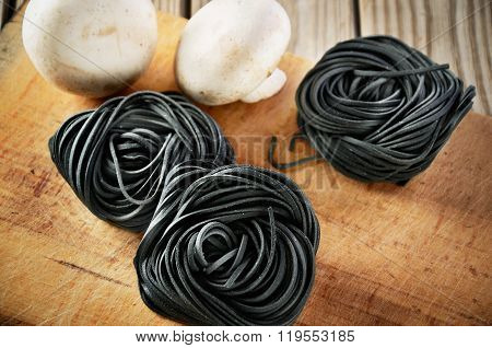 Three Servings Of Pasta With Black Cuttlefish Ink And Two Mushroom On A Chopping Board