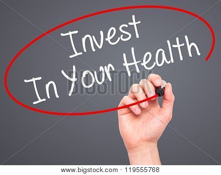 Man Hand Writing Invest In Your Health With Black Marker On Visual Screen.