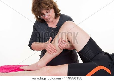 A Chiropractor Female Stretches A Man's Leg In A Surgery