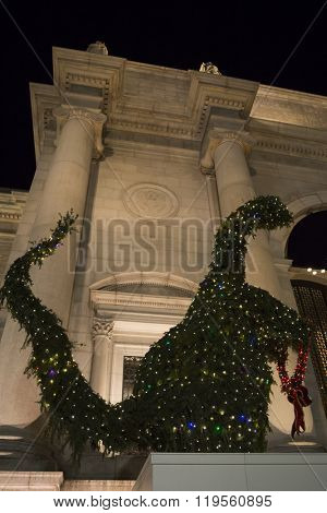 NEW YORK - NOV 25 2015: A dinosaur topiary made from evergreen branches with lights by the entrance of the Museum of Natural History the night before the 89th Thanksgiving Day Parade in Manhattan.