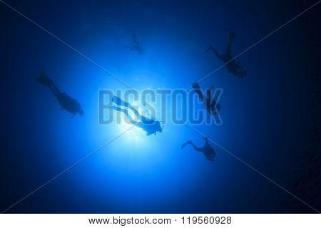 Scuba diving group silhouette against sun