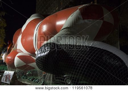 NEW YORK - NOV 25 2015: Red Ranger from Mighty Morphin Power Rangers balloon tied down on its side with sandbags and netting during Macys Giant Balloon Inflation event the day before Thanksgiving.