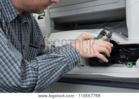 Hands Of A Male Trying To Repair The Office Printer