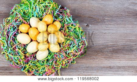 Easter Eggs On Top Of Colorful Mache Paper With Rustic Wooden Boards