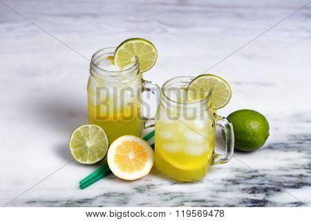 Homemade Lemonade In Jar Glasses On White Marble Stone Background