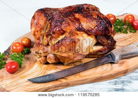 Large Whole Chicken Ready To Be Carved On Wooden Server Board