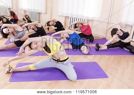Sport And Fitness Concept. Group Of Seven Female Athletes Performing Stretching Exercises On Sport M