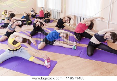 Fitness Concept. Group Of Seven Female Athletes Performing Stretching Exercises On Sport Mats