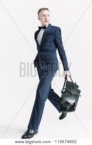 Business People Concepts. Young Caucasian Handsome Man With Bag Striding Against White