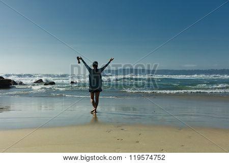 Woman Walking Towards Ocean Waves While Barefoot