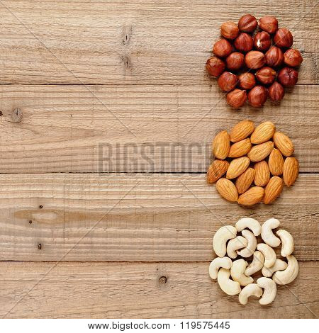 Filberts, Almonds And Cashew Nuts On Wooden Table