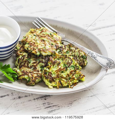 Zucchini Fritters On A Ceramic Plate On A Light Wooden Background. Healthy, Vegetarian Food