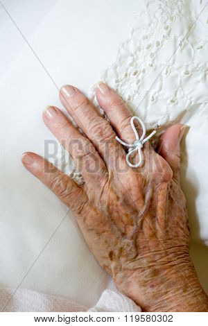 String tied on finger of elderly woman